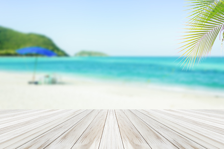 wood deck on blur blue sky and beautiful tropical beach of Summer sea background  .The sand is empty