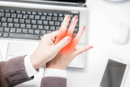 The lock finger of a young businessman sitting with a computer all day.Palm pain from working with a young businessman's computer.