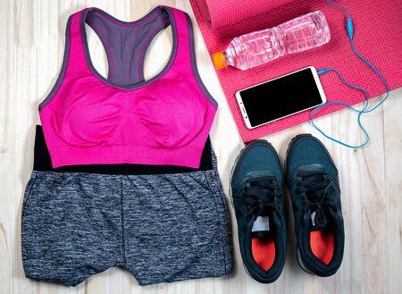 Robe d'exercice pour femmes Chemise rouge et pantalon noir Utilisez pour porter une séance d'entraînement. L'eau potable, les écouteurs et l'horloge utilise une minuterie placée sur un fond blanc. Banque d'images