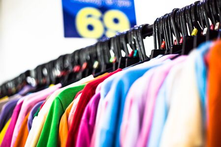 Rainbow colors fashion clothing on hangers at the show.