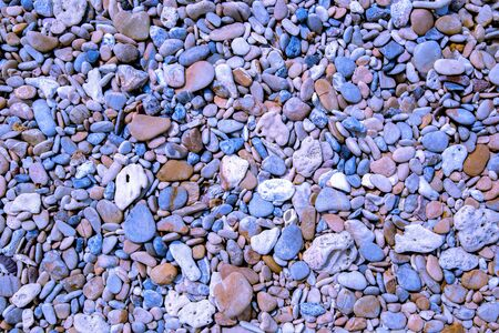 Natural vintage colorful pebbles background on beach in summer for wall design and natural background business concept in summer. Banco de Imagens