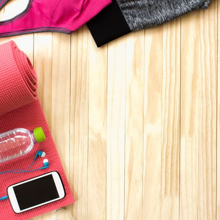 Sports bra Pink for women is set , with smart phone ,headphones,yoga mat,Measure the waist and water on wooden floor. Copy space for text input on health care and fitness.