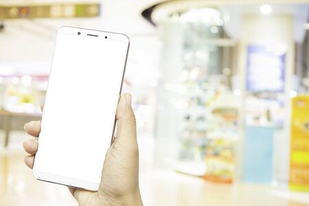 Hand shows smartphone in horizontal position on blurred shopping mall background,concept business shopping mall.Hand shows smartphone with clipping path. 写真素材