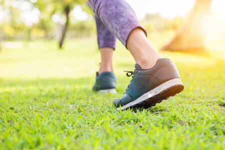 Portrait of beautiful Women running exercising in the park on green tree and green grass background at sunny bright light. 写真素材