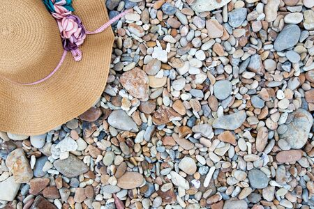 Summer Accessories Have a pink hat in the summer. Placed on a nature Stone beach  floor texture background. Concept of business in the summer. 写真素材