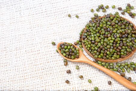 nature green mung beans in wooden spoon on white sackcloth and wooder  background