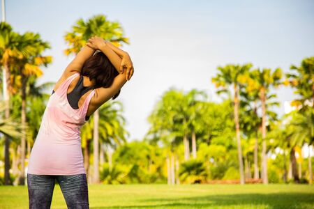 Portrait of beautiful Women exercising in the park on green tree and green grass floor background at sunny bright light.