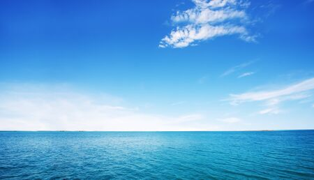 Beautiful white clouds on blue sky over calm sea with sunlight reflection in sea . The day when the sea waves calm, clear sky.