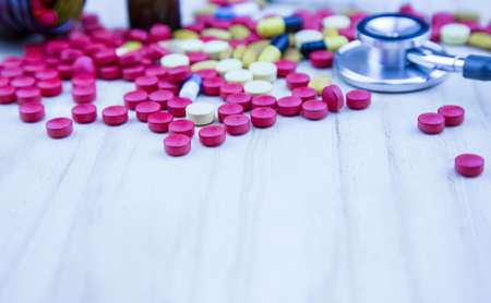 Antibiotics contain blue pills, yellow-red or capsules on white wood texture background with copied clearance. Medication in healthy containers, antibiotics and dangerous drugs. Banco de Imagens