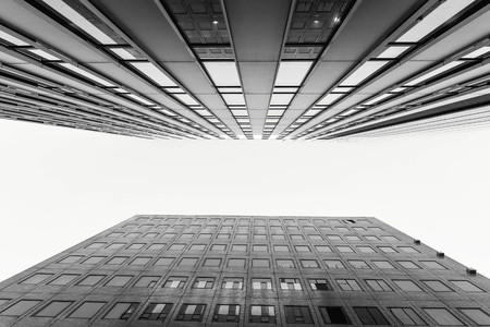 bldg: Glass surface of skyscrapers view in district of business centers with reflection on it, black and white Stock Photo