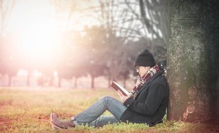 大きな木の下で本を読んでアジア男