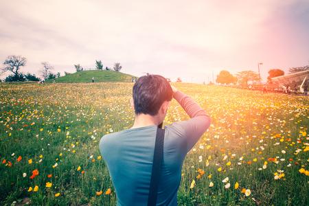 カメラマンがカメラを持って、花を撮影します。