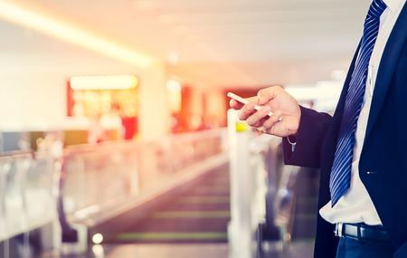 zakenman is Zakendoen op mobiele telefoon, terwijl hij op luchthaven zit in de buurt van venster met zonnestralen tijdens zijn dienstreis.