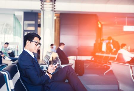 Geschäftsmann ist Doing Business auf dem Handy, während in Flughafen in der Nähe von Fenstern mit Sonnenstrahlen während seiner Geschäftsreise sitzen.