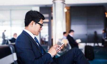 자신의 비즈니스 여행을하는 동안 태양 광선 창 근처에 공항에 앉아있는 동안 비즈니스 남자가 휴대 전화 사업을하고있다.