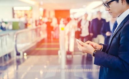 ビジネスマンはビジネスを行う携帯電話の中に座っている空港と太陽光線の窓の近く彼の出張中。
