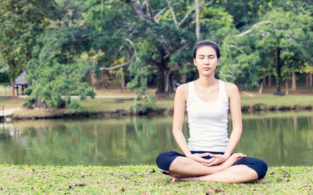 mid morning: Young woman doing yoga in morning park
