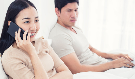 Couple in bed, happy smiling man turned her back to man, reading message on phone from her lover, worried woman lying next to her, trying to peek at screen. Cheating and infidelity concept