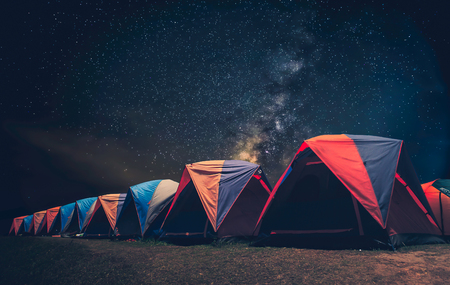 Tourist near his camp tent at night under a sky full of stars. Orange illuminated tent Фото со стока - 99044341