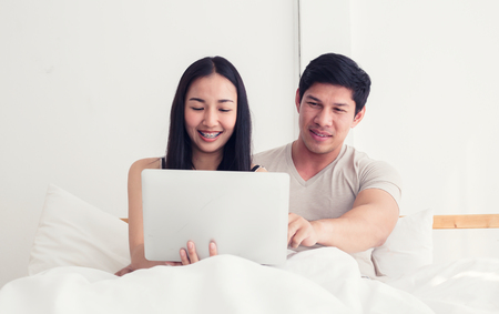 Couple in bed, happy smiling man turned her back to man, reading message on phone from her lover, worried woman lying next to her, trying to peek at screen. Cheating and infidelity concept Archivio Fotografico - 101956685