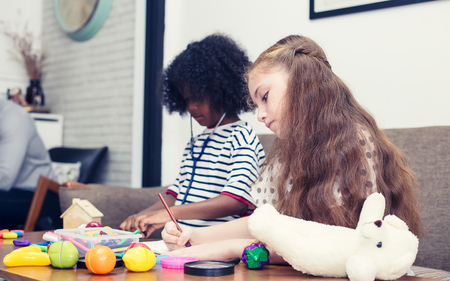 Two girls drawing a picture and Little Girl Holding Magnifying Glass Smiling.have copy space in enter text.