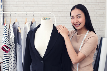 Fashion designer measuring a dress. Shallow depth of field. Young woman choosing clothes and measure clothes on a puppets