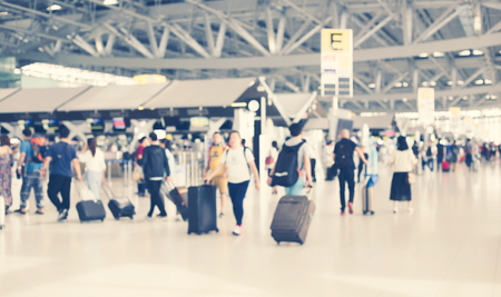 people carries luggage at the airport terminal.City commuters. High key blurred image of tourist going abroad after work in holiday. Unrecognizable faces, bleached effect. Archivio Fotografico - 106253595