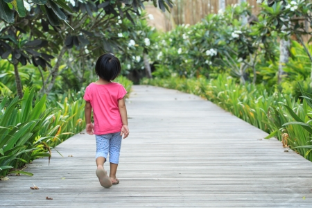 A rear view of toddler girl walking straight by her own photo
