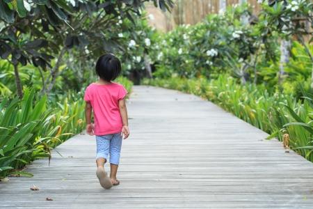 niños caminando: Una vista posterior de la muchacha del niño caminando derecho por su propia Foto de archivo
