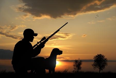cazador: Hunter con sus siluetas de perro sobre fondo sunset