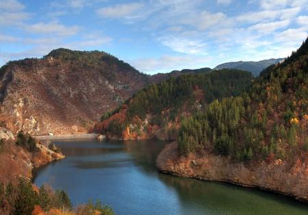 Autumn view dam Teshel situated in mountain Rodopi, Bulgaria photo