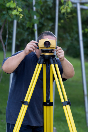 leveling: Land surveyor measuring with digital level device