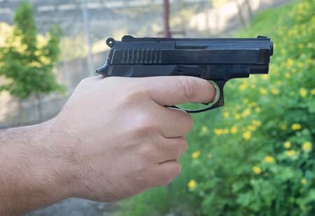 automatic pistol: Detail of mans hand holding automatic pistol