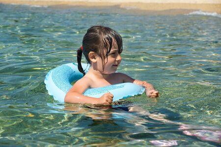 nadar: Niño con el anillo de divertirse flotando en el mar Foto de archivo