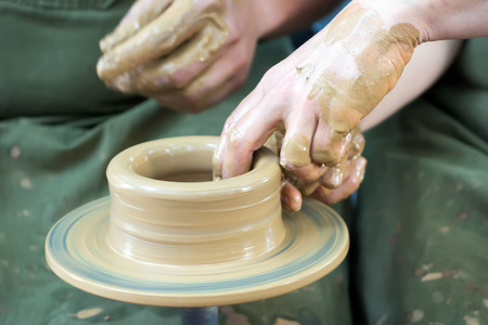 novice: A potters hands guiding a novice hands to help him
