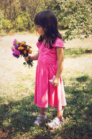 field of flowers: Little girl holding bouquet of field flowers