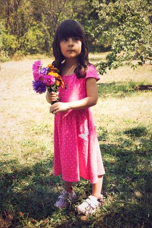 champ de fleurs: Petite fille tenant bouquet de fleurs des champs Banque d'images