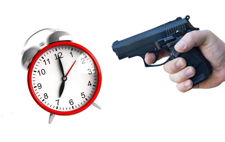 hand gun: A hand with pistol ready to fire at an ringing clock