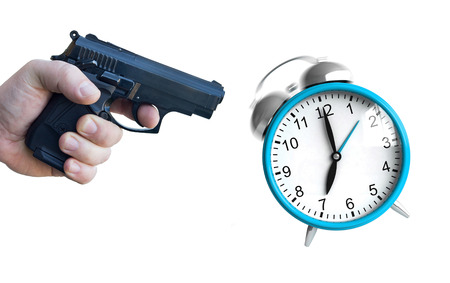 ringing: A hand with pistol ready to fire at an ringing clock