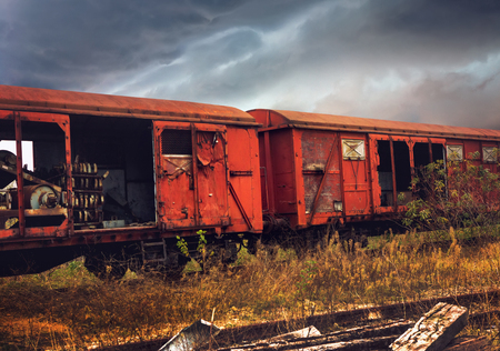 Abandoned train composition on dramatic clouds background Stock Photo