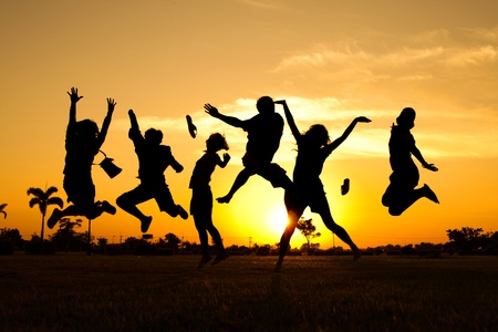 Teenagers jumping over sunset photo