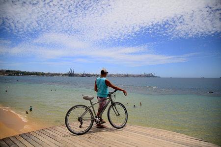 salvador, bahia, brazil - january 1, 2021: man with bicycle observes the waters of Baia de Todos os Santos at a pier on Boa Viagem beach in the city of Salvador.