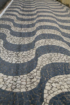 sidewalk with mosaic design made with portuguese stones is seen in the neighborhood of Itapua, in the city of Salvador.