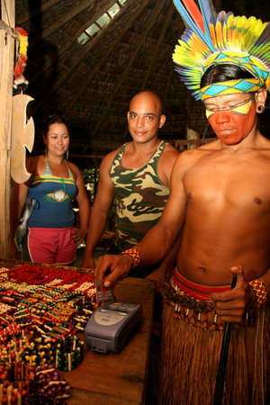 porto Seguro, bahia / brazil - february 21, 2008: Pataxo Indians use credit card machines during sales and souvenirs for tourists visiting the Jaqueira village in the city of Porto Seguro.