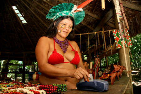 porto Seguro, bahia / brazil - february 21, 2008: india pataxo da audeia Jaqueira in the city of Porto Seguro, is seen using a credit card to pay for souvenirs bought by tourists.