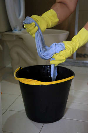 person wearing a rubber glove and holding a cloth next to a bucket while cleaning a bathroom in a residence in the city of Salvador.