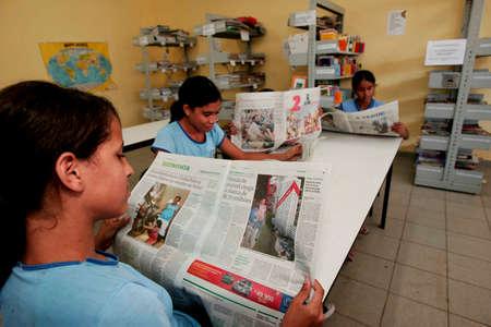 porto Seguro, bahia / brazil - november 16, 2009: Public school students are seen reading a newspaper in a library in the city of Porto Seguro. 新聞圖片