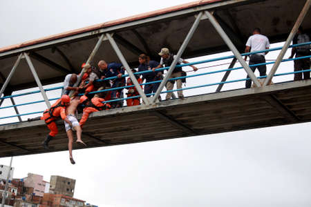 salvador, bahia / brazil - may 22, 2015: members of the fire brigade are seen during the rescue of a man who attempted suicide from a walkway in the city of Salvador. Éditoriale