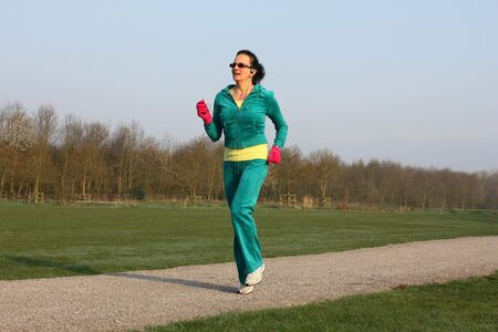 Woman running outdoors with her MP3 headset photo