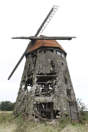 wind powered building: Front view of an old scary abandoned wooden windmill Stock Photo